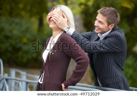 Young happy couple having fun at the park. Man puts his hands over girl's eyes. - stock photo