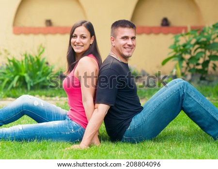 Young happy couple having fun in the garden on beautiful spring day. - stock photo