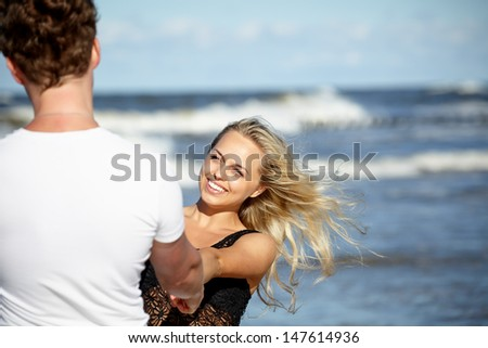 Young happy couple having fun on the beach. - stock photo