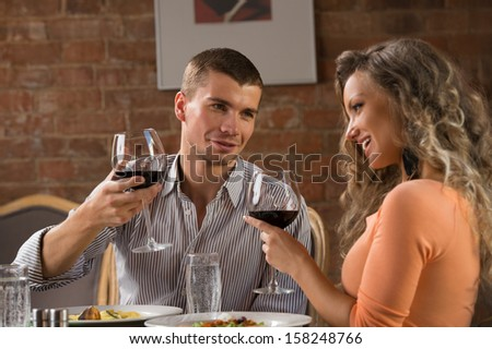 Young happy couple having romantic date at restaurant - drinking wine and eating gourmet food