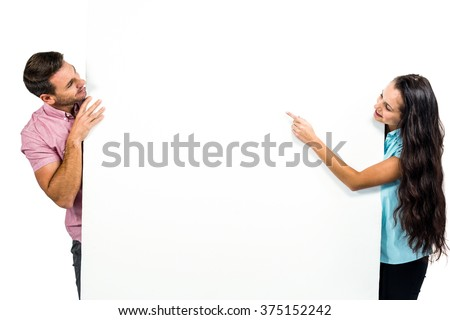 Young happy couple holding white sheet on white screen - stock photo