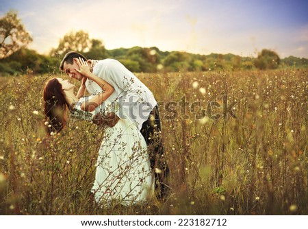 Young happy couple hugging on the field, on the sunset
