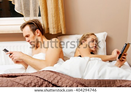 Young happy couple in a bed with mobile phones - stock photo
