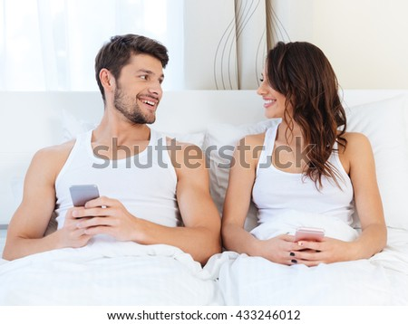 Young happy couple in a bed with mobile phones looking at each other at home in a bed with mobile phones - stock photo