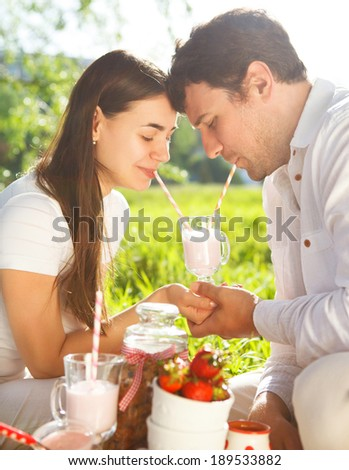 Young happy couple in love drinking milk shake at spring picnic in spring day. Outdoors portrait