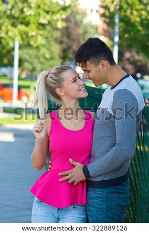 young happy couple in love kissing and hugging outside