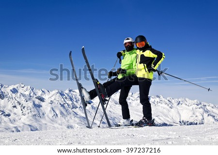 Young happy couple in snowy mountains - stock photo