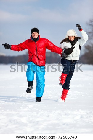 Young happy couple jumping outdoors. - stock photo