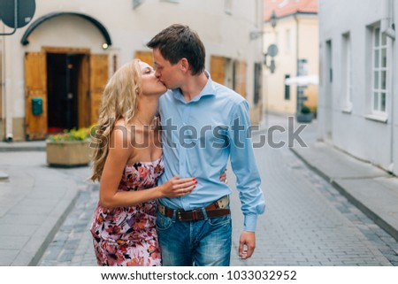 Young happy couple kissing while walking on the street. Smiling man and woman having fun in the city.