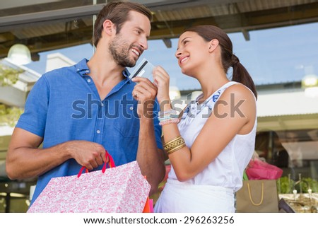Young happy couple looking each other after shopping holding a credit card - stock photo