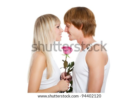 Young happy couple love smiling with pink rose, looking to each other and hug kiss touching nose, isolated over white background - stock photo
