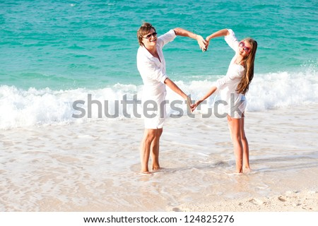 young happy couple making heart shape on tropical beach. honeymoon - stock photo