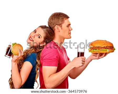 Young happy couple man and woman holding big hamburger and cola . Fastfood concept. Isolated. - stock photo