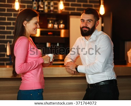 Young happy couple met in bar and talking with a cup of coffee - stock photo