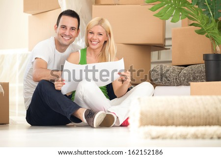 Young happy couple moving into their new home with plan  - stock photo