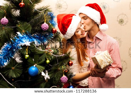 Young happy couple near a Christmas tree - stock photo