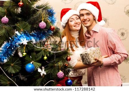 Young happy couple near a Christmas tree - stock photo