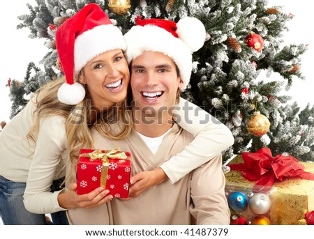 Young happy couple near  a Christmas tree. Isolated over white background - stock photo