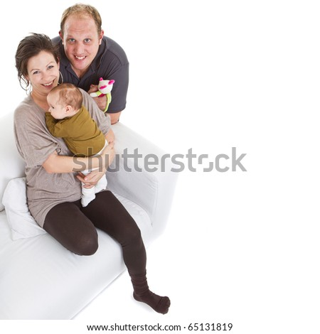 Young happy couple on a couch with their baby over white background.