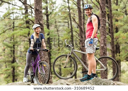 Young happy couple on bikes looking at camera in the nature