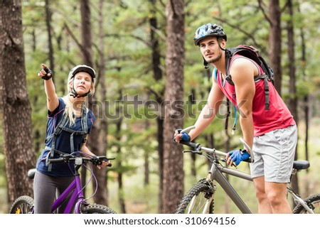 Young happy couple on bikes looking away in the nature