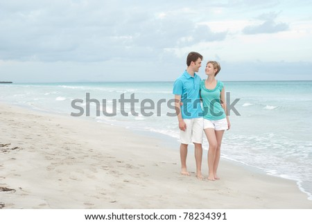 Young happy couple on the beach - stock photo