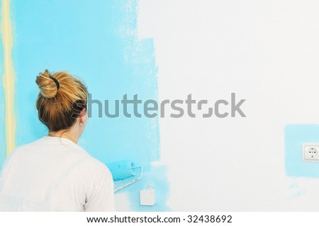 young happy couple painting their new home interior