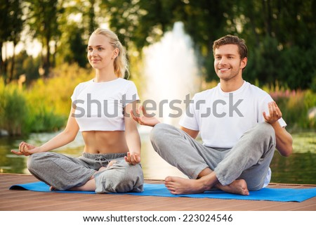 Young happy couple practising yoga and sitting in lotus pose with a beautiful green scenery of park on background - stock photo