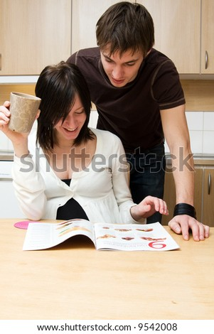Young happy couple reading magazine in the kitchen
