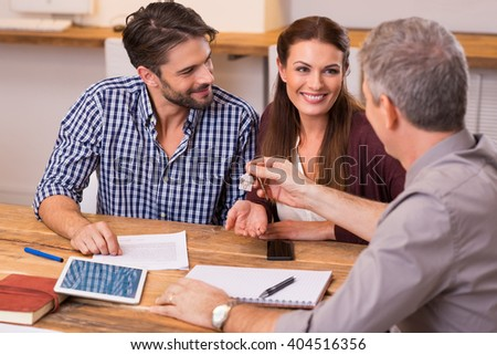 Young happy couple receiving house keys from real estate agent. Giving keys of new house to young couple. Smiling couple signing financial contract for mortgage. - stock photo