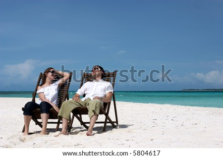 Young happy couple relaxing at tropical white sand beach - stock photo