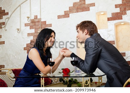 Young happy couple romantic date at restaurant, celebrating hold hands smile lover looking to each other - stock photo