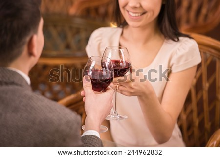 Young happy couple romantic date drink glass of red wine at restaurant.