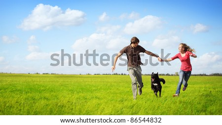 Young happy couple running on a green meadow with a black dog - stock photo