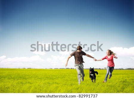 Young happy couple running on a green meadow with a dog - stock photo