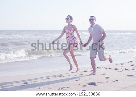 Young happy couple running together among a seashore at sunny day. Casual clothes - stock photo