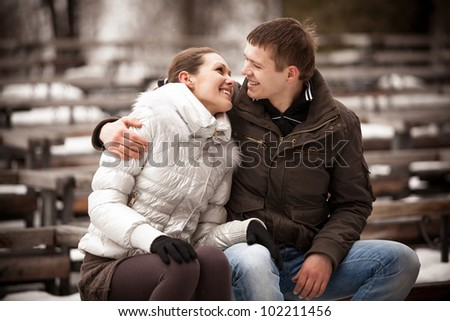 Young happy couple sitting on bench and looking at each other - stock photo