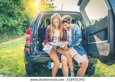 Young happy couple sitting on car looking at map - Adventure in the nature, two hikers looking at the road on a cross-country vehicle - stock photo