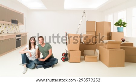young happy couple sitting on floor in new apartment with moving boxes around them - stock photo