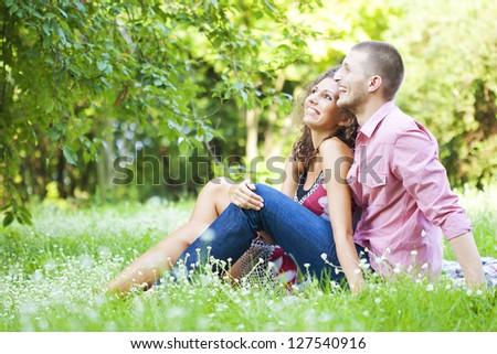 Young happy couple sitting on ground enjoying spring in the park - stock photo