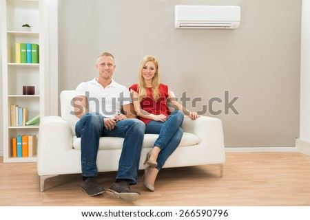 Young Happy Couple Sitting On White Sofa  - stock photo