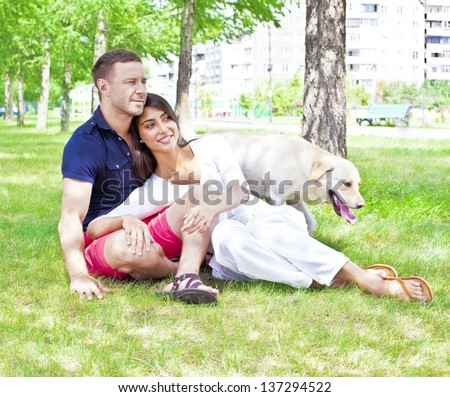Young happy Couple sitting with Dog at the summer park