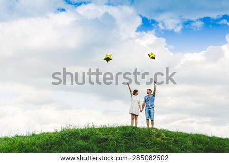 Young happy couple standing on a green meadow with ballons