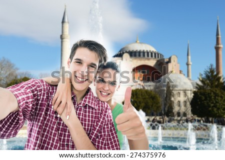Young, happy couple taking a self portrait photo, selfie, in front of the Aya Sofia mosque in Istanbul, Turkey - stock photo