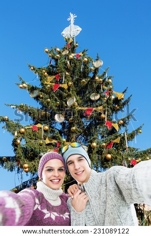 Young, happy couple taking a self portrait photo, selfie in the front of the Christmas tree - stock photo