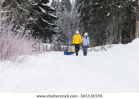 Young happy couple walking in the park in winter. Beautiful lovers ride on a roller coaster tubing. A man and a woman go through the forest and hold each other's hands.
