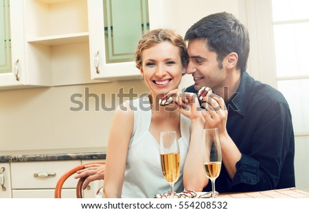 Young happy couple with champagne and cakes at home