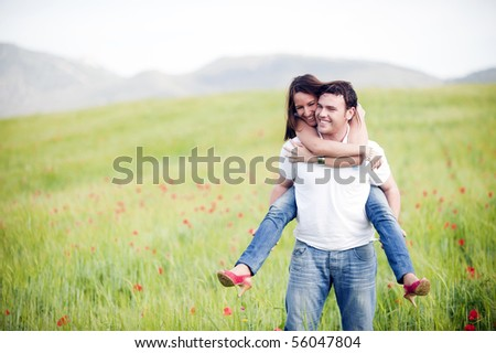 Young happy couple with her at piggiback un spring field - stock photo