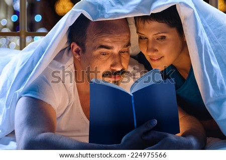 young happy couple with light book on garland background - stock photo