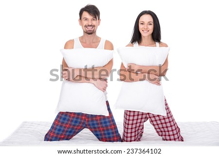Young happy couple with pillows, isolated on white background. Looking at the camera and smiling. - stock photo